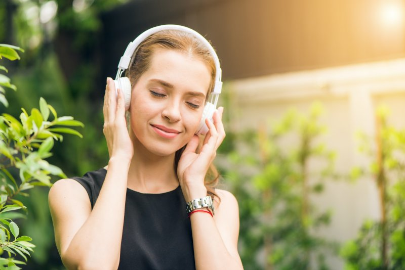 Woman smiling and listening to relaxing music