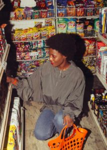 Happy woman shopping for goods in convenience store