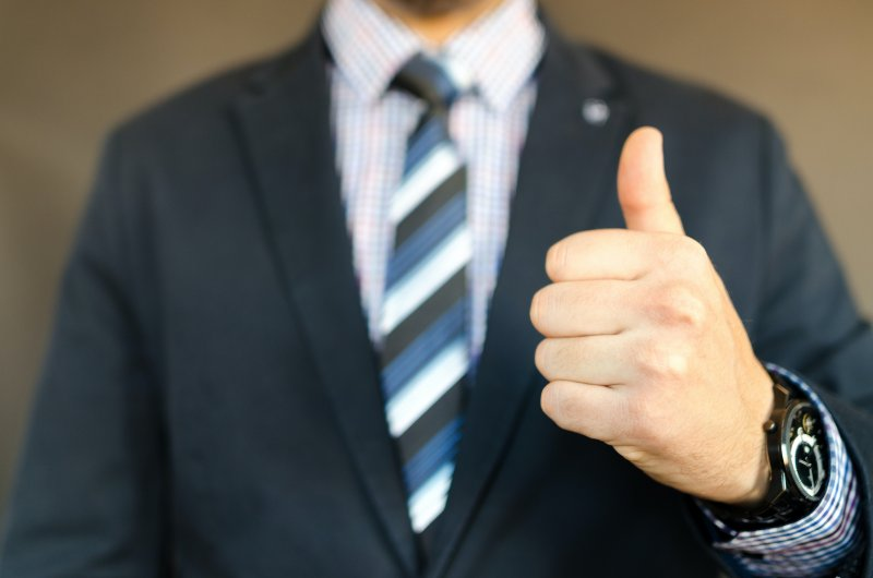 businessman giving thumbs up for honesty