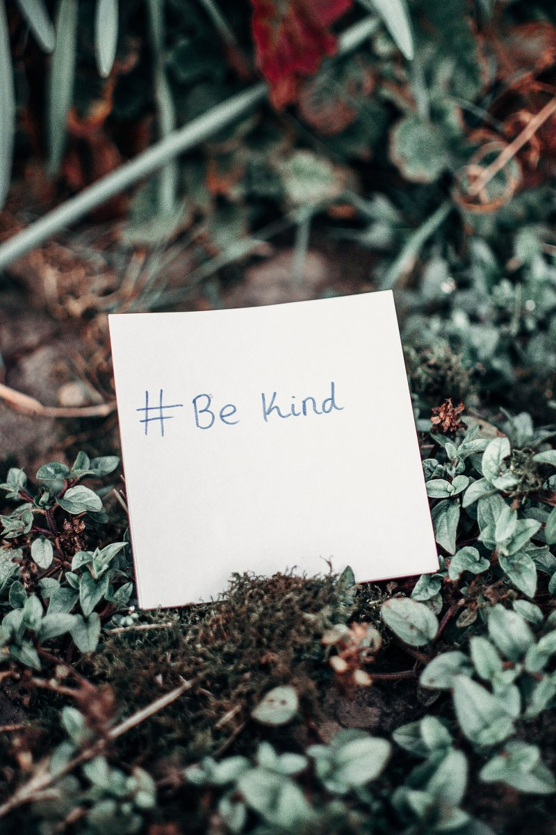 #be kind on white paper against floral background